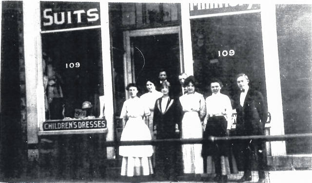 Then – This is a circa 1911 photo (#2005) of the original location of the Boston Store at 109 Scioto St., Urbana. The clothing and department store was opened in 1910 by Harry Bernstein and Martin Reich at this location. Martin Reich is on the far right. The store was called the Fair Store. The store moved to 121 N. Main St. in 1917 and was named the Boston Store.
