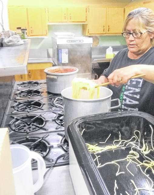 Sandy Hulbert cooks spaghetti to be delivered to residents of Settlers Ridge earlier this week.