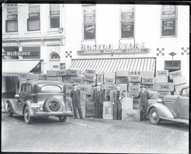 Then – This is a 1939 photo (#0187) of the Boston Store, 121 N. Main St., Urbana. Standing in front of boxes of Ball Band footwear are, left to right, Francis Collins, Harry Bernstein, Malcolm Reich and Martin Reich. Upstairs was the Springfield Loan Co. Next door was the Scherer Clothing Store, above which was the office of Dr. E. E. Meyer, dentist. Related photos in the Champaign County Historical Society archives are 0188, 0221, 2006, 2007, 2008 and 2009. The Boston Store was first located at 121 N. Main St. in 1917. What was the original location of the Boston Store? Answer and photos in a later installment of Then-Now.
