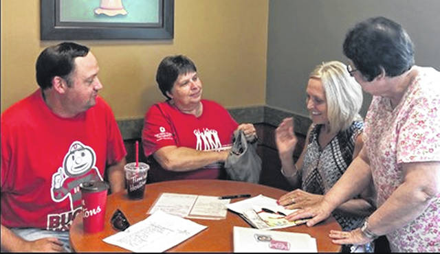 Members of the Ohio State Alumni Club of Champaign County go over plans for their Summer Send-Off at 6 p.m. Sunday, July 28, at Pretty Prairie Farm, 4440 Prairie Road, south of Urbana. From left are President James Landenburg, Treasurer Chris Harmison, Event Chair Jill Michael and Vice President Julie Balmer. Summer Send-Offs bring Buckeye students and alumni together in the spirit of Scarlet and Gray camaraderie. At these events, alumni clubs around the world share lessons learned from experiences at OSU and mentor incoming students. In June, the club sponsored a bike ride to raise funds for scholarships to be presented to four incoming freshmen. All OSU alumni in Champaign County are invited to attend the free Send-Off picnic catered by Rudy's Smokehouse. Those wishing to attend are asked to RSVP to Jill Michael at jill@michaelfamilyfarms.com or 937-215-5013 by July 25.