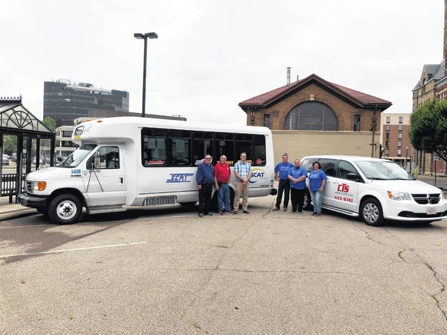 Representatives of the Champaign Transit System and Springfield City Area Transit stand by their vehicles at the transfer site.