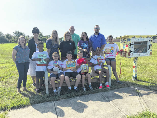 "Wood workshop campers who created the community's newest ""Little Free Library"" are, in front from left, Jae Duke, Hank Huffman, Aiden O'Neal, Garrett Naylor, Isabella Moxley and Nora Mowrey. With them at the ribbon-cutting are, in back from left, Sara Neer, Rachel Casey, Stacey Logwood, Austin Wick, Paul Waldsmith, Nicky Naylor and Brett Spriggs."