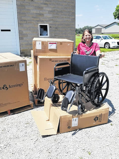 Theresa Cornett of Honor Flight stands next to one of the 10 wide wheelchairs purchased for travelers.