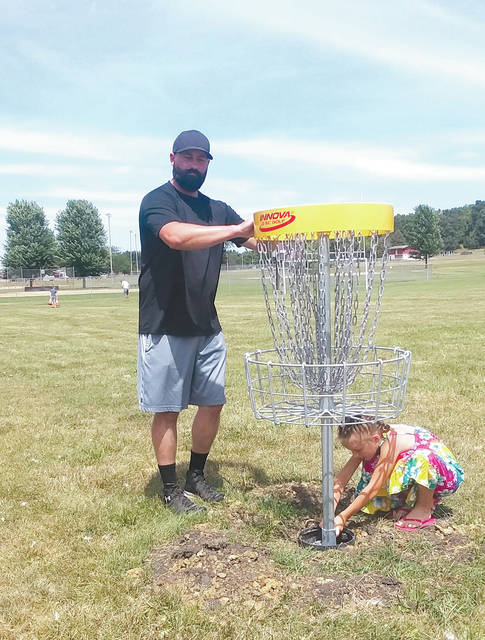 Hilltop Disc Golf Club President Tommy Yoder and niece Vyla Yohey set the baskets on the new Valley 9 disc golf course at Melvin Miller Park on Sunday. The course is beginner friendly, kid friendly and more handicap accessible than the original 18-hole course that goes into the woods. The club has more projects in the works to further improve the nine-hole course, including tree planting this fall.