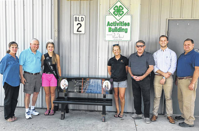 A new bench at the Champaign County Fair honors Ohio Fairs Queen Lora Current, also queen of the 2018 Champaign County Fair. The bench's permanent home is outside the Perpetual Activities Building. Bench sponsors Vernon Family Funeral Homes and Set N Stone Monuments commemorated the bench earlier this week. Shown, left to right, are Tammy Vernon, Chuck Havens, Lora Current, Victoria Vernon, Cliff Vernon, Colin Vernon and Randy Leopard.