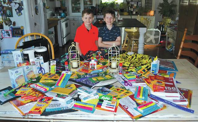 Twin brothers Joshua and Jake Blakeman, starting fourth grade this week, stand behind $130 worth of school supplies they donated to Urbana Elementary School for students in need. Their mother, Tina Blakeman, began collecting supplies at her shop, The Vintage Traveler, then the boys collected donations from 23 downtown businesses.