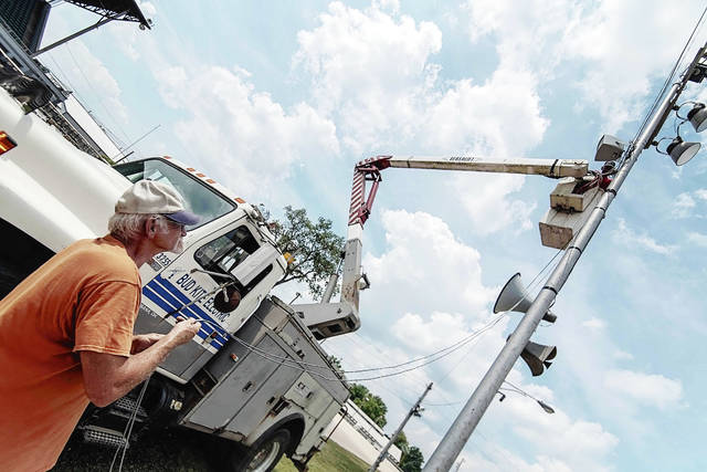 Workers from Bud Kite Electric run new speaker wire at the Champaign County Fairgrounds on Monday.