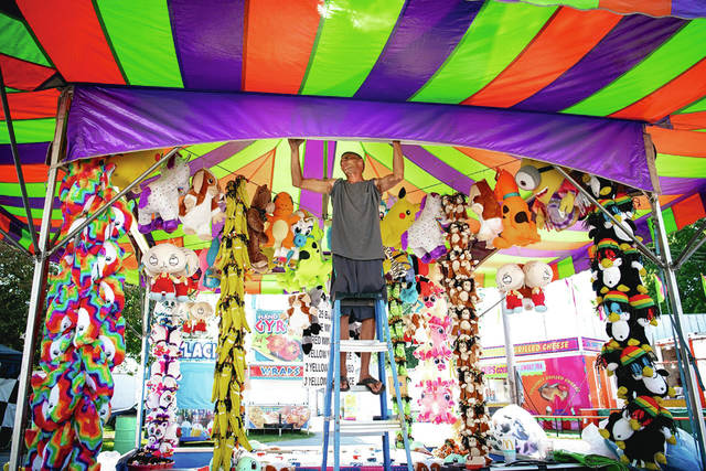 "A worker puts the finishing touches on the ""Buoy Pitch"" game in preparation for players visiting the Champaign County Fair, which opened today and run through Friday, Aug. 9. See inside for more photos and the weekend's fair schedule."