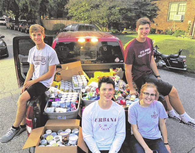 UHS DECA Members pose by the total amount of donations received at the September 20 Community Night. Pictured from left are Austin Rooney, Gavin Spence, Paige Martinez and Grant Hower.