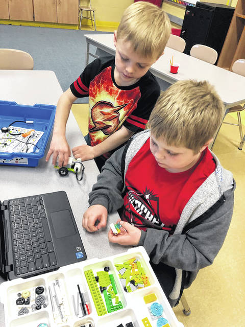 Second graders Caleb North and Coen Shelton build and program a WeDo robot.