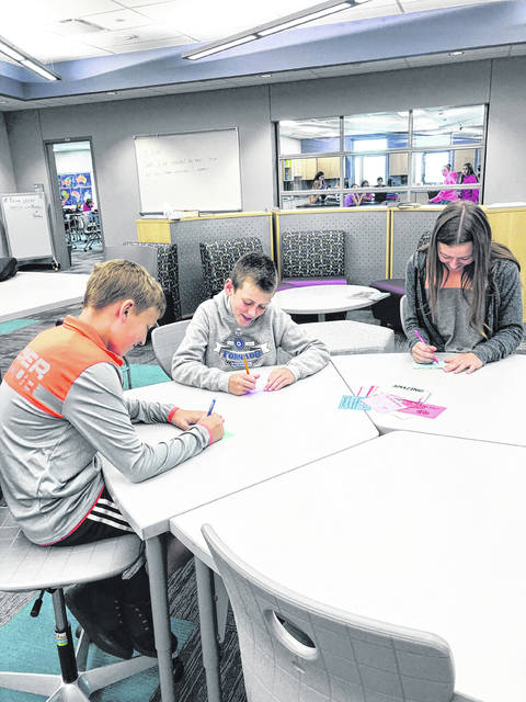 Cayden Prosser, Brody Donahoe and Brenna Fife (shown left to right) write notes of encouragement for the new kindergarteners for National Encouragement Day.