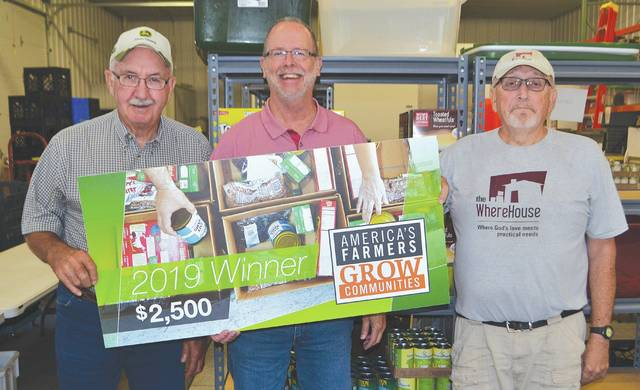 Jim Virts (left) and his wife, Nancy (not pictured), were awarded $2,500 from America's Farmers Grow Communities, sponsored by the Bayer Fund, which they chose to donate to the nonprofit WhereHouse Food Pantry. Jim Lillibridge, senior pastor of Urbana United Methodist Church (center) and WhereHouse director Ted Herndon (right) said they plan to use all of the money to buy food for families in need, and that the WhereHouse has already served 2,612 households so far this year. In addition to the food pantry, WhereHouse also sponsors a community dinner on the 14th of every month from 6-7 p.m. at their facility at 110 W. Church St.