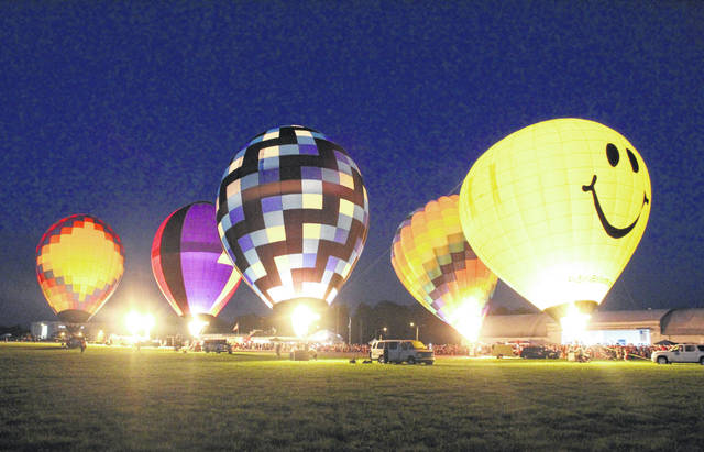 Hot-air balloons will fly over Urbana Oct. 4-5 when the Champaign County Balloon Fest lands at Grimes Field. In this photo from 2018, about 200 million BTUs of propane fuel this balloon glow display just after sunset.