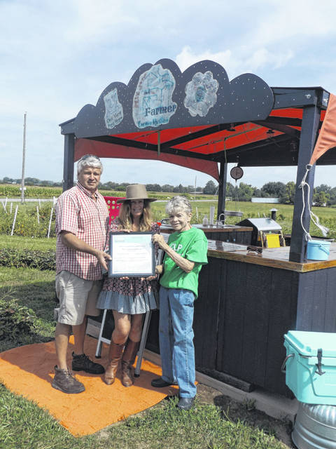 Ardell Price, president of Champaign Land Preservation, presents a Certificate of Appreciation to Mark Runyan and Pam Bowshier of Hippie and the Farmer. For many years, they have contributed prizes of their produce to winners of drawings at the Champaign Land Preservation booth at the Champaign County Fair. Pictured from left to right are Mark Runyan, Pam Bowshier, Ardell Price at Hippie and the Farmer retail outlet on state Route 54.