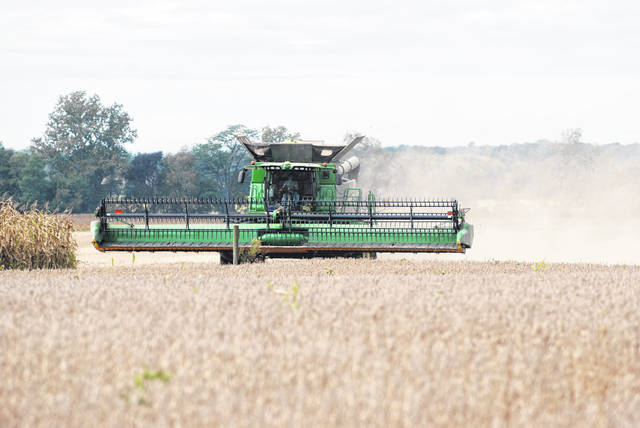 A farmer is pictured harvesting a field on River Road west of Urbana on Wednesday. The Champaign County Sheriff's Office is asking motorists to share the road with farm equipment and be extra cautious on the roads this season.