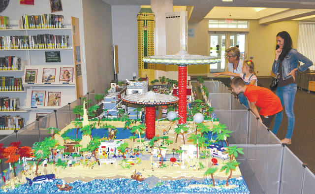 Librarian Pat Eubanks looks at the Champaign County Library's Lego display with 6-year-old Vyla Yohey, 9-year-old Dexyn Yohey and their mom, Julie Yohey.