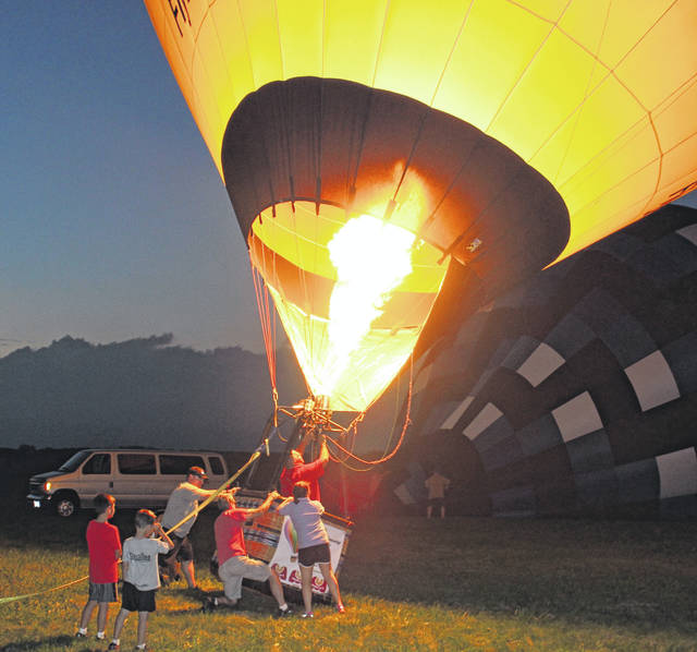 "Volunteers help hold down ""Smiley"" - a 100,000 cubic-foot balloon that was on hand for the Balloon Fest 2018."
