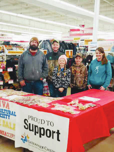 Tyler (center) and Monica Slaven (far right) and crew pose at one of their bake sales that helps support their annual grassroots toy drive.