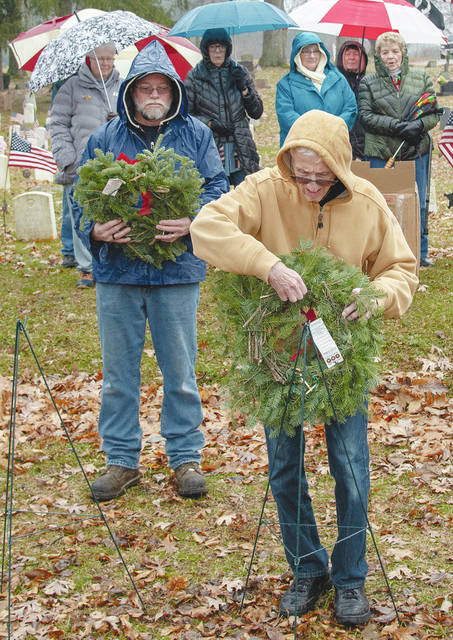 Frank Giampetro (foreground) places a wreath representing The Merchant Marines during 2018's Wreaths Across America ceremony at Oak Dale Cemetery as others behind him observe.