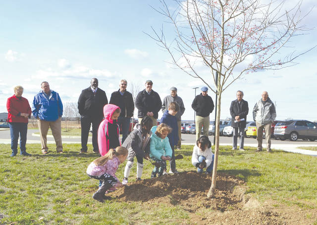 Urbana second graders Meghan Haskins, Rosealee Raines, Addison Gavin, Esther Moore, Gage Gibson and Keisha Neri help plant trees donated to the Urbana K-8 building by the Urbana Rotary Club on Friday.