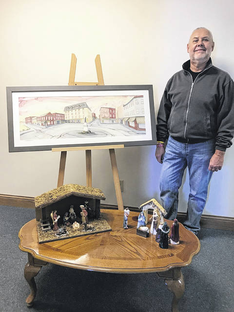 "Mike Henson, Messiah Lutheran Church's organizer of No Room at the Inn, stands by Scott Kirby's ""Monument Square"" painting to be raffled and by two of the hundreds of nativity sets that visitors will see at the Dec. 8 event."