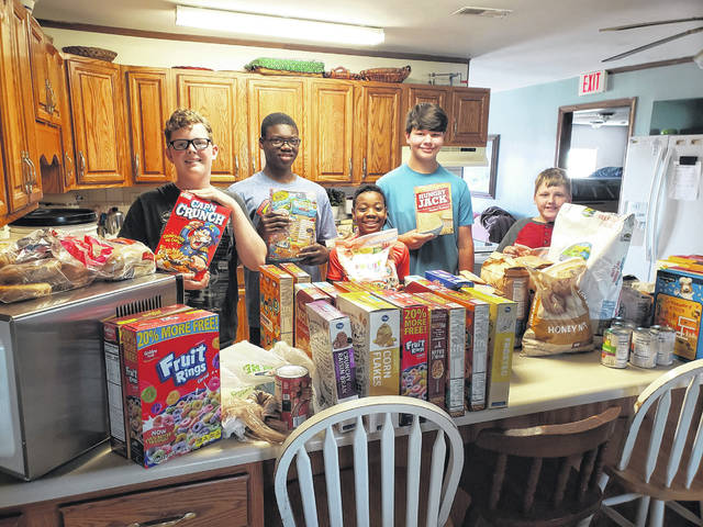 Operation Rebirth students help unpack a donation of groceries. Match Day funds support expenses of the Christian boarding school for boys near St. Paris.