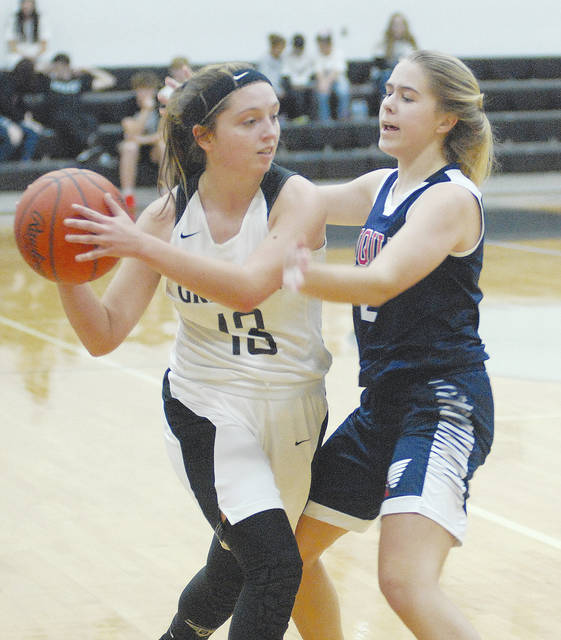 Graham's Katelyn Nash (left) is pressured by Piqua's Elise Cox during Tuesday night's game at GHS.