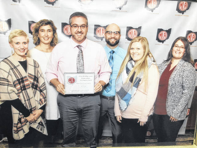 Accepting the award on behalf of Graham Middle School are teachers Polly Trenor and Katie Setty, Principal Nick Guidera, Director of Teaching and Learning Chad Lensman, and teachers Emilee Tannyhill and Amy Weinert.