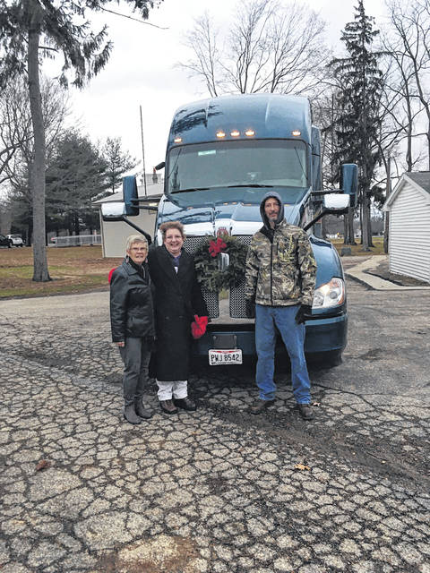 DAR Regent Kim Snyder and Past Regent and Chair Pat Detwiler stand with driver and veteran Rodney James at the front of the semi carrying the wreaths.