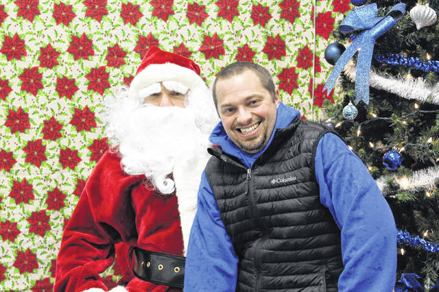 Santa is shown with one of his Apple Farm Service elves during a visit to Mechanicsburg during a past Christmas season.