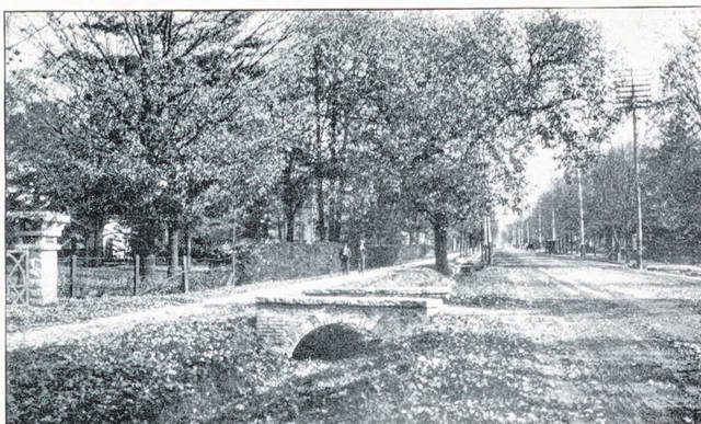 Then – This is a circa 1910 postcard street scene (#A1030) looking east on Scioto Street from the intersection with Happersett Street. The stone post on the left edge of the photo marks the driveway entrance to the large house that is midway between Scioto and East Court streets. This is likely the same post visible in the Now photo. Note the stone bridge over the ditch that runs on the north side of the street. Horse and buggies are traveling the unpaved street.