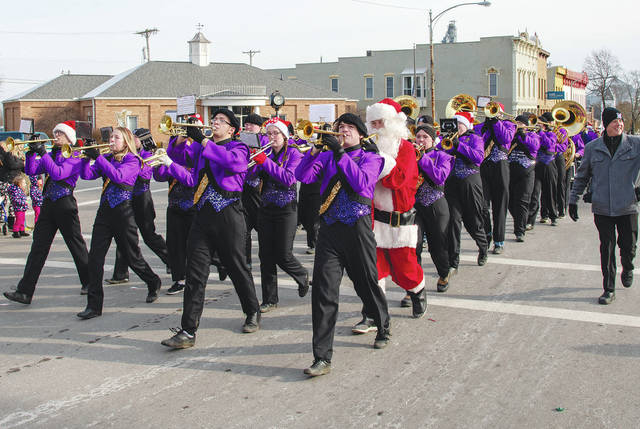 The Mechanicsburg High School Marching Band keeps the atmosphere musical and festive during the parade at Christmas in the Village on Dec. 8, 2018.