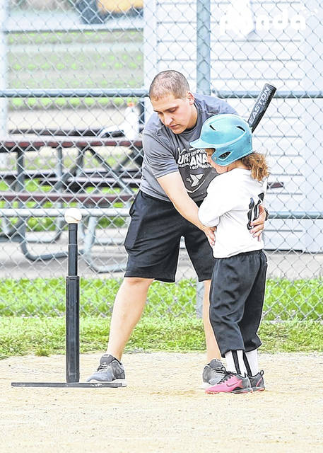 Coach Augie Martinez instructs in T-ball action during a session last summer