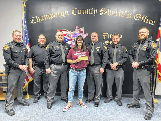 "Amy Johnson of Champaign County Special Olympics accepts a $520 check from Sheriff Matthew Melvin and members of the county Sheriff's Office who ignored their razors and participated in ""No Shave December"" to raise funds for local Special Olympics activities. The December fundraiser followed a similar one in November when the sheriff's office teamed up with Judge Brett Gilbert for ""No Shave November"" and raised $1,000 for the Cancer Association of Champaign County."