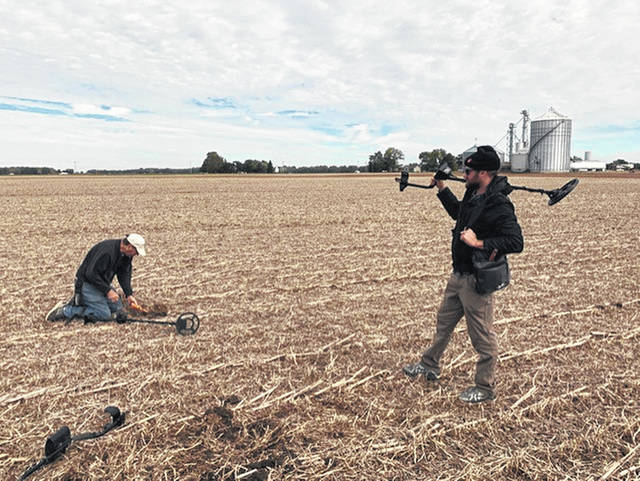 Adam, standing, and Frank Drain explore a crash site south of U.S. Route 36 just west of the Mad River. Adam's brother, Kevin Drain, holds the camera. Frank Drain is one of the principals in the B-17 restoration project.