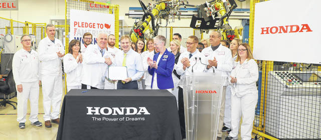 Rick Schostek, executive vice president of Honda North America Inc., and U.S. Rep. Jim Jordan (R-Urbana) hold the Pledge to America's Workers as Dr. Doreen Larson, president of Edison State Community College, and Honda associates look on.