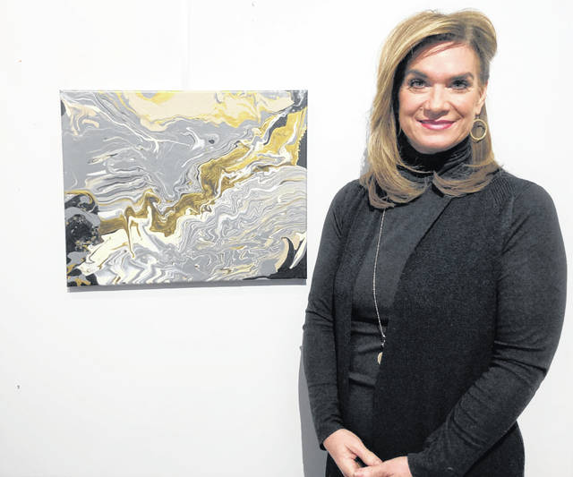 Andrea Russell poses with her art, an acrylic pour.