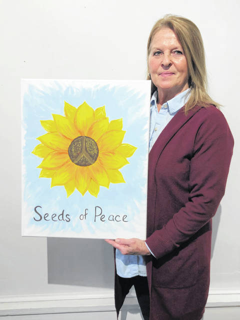 Bev Titus poses with her sunflower art, depicting the seeds of peace.