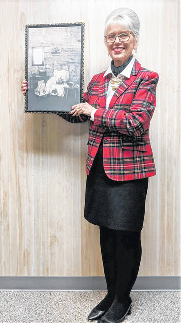 Chris Phelps poses with her art, a salute to the value of 'second hand' items.
