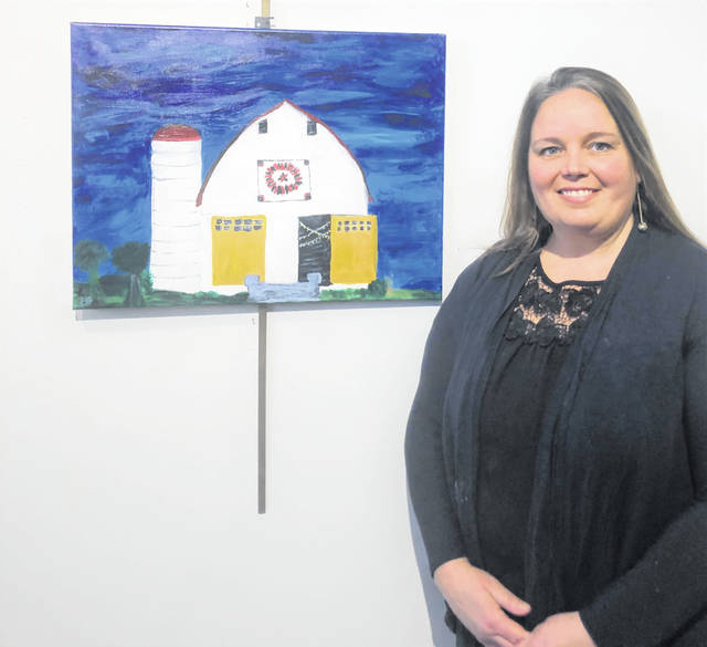 Elizabeth Smith poses with her art, which depicts a barn at her farm.