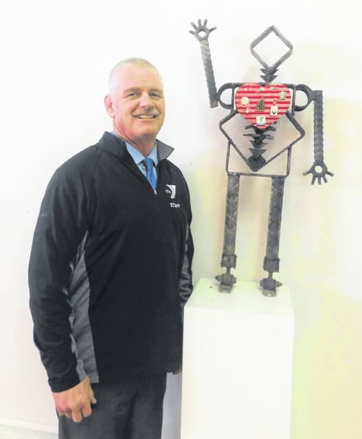 Jerry Fetherolf poses with his art — a small window of his life, his heart attack in 2013, and his transformation from an out-of-shape guy to a person who has found the importance of staying fit.