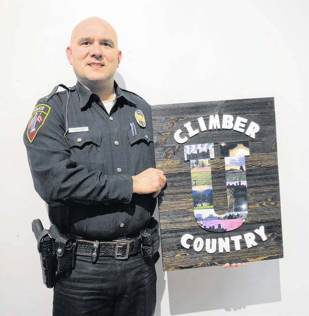 Josh Jacobs poses with his art, which reinforces the declaration that he's proud to be from 'Climber Country!