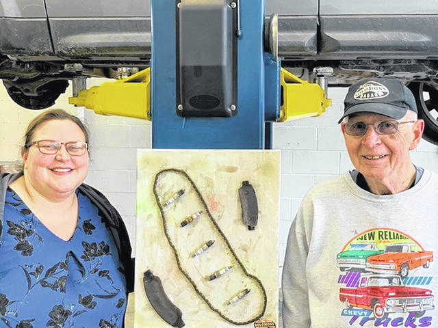 """Katie Neer poses with her art, inspired by her auto repair business. Also pictured with Neer is Henry """"Bud"""" Tomlinson."""