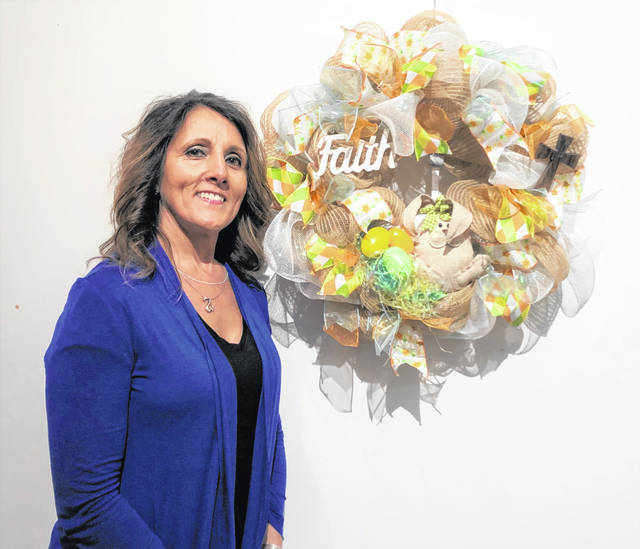 Lisa Dunham poses with her artwork. Dunham started making wreaths a couple years ago when her son got married and it has evolved into a hobby.