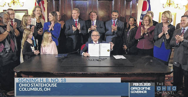 In this screenshot from The Ohio Channel, Ohio Gov. Mike DeWine signs a bill into law benefitting veterans as bill author Rep. Nino Vitale (R-Urbana) is pictured standing to the right of DeWine.