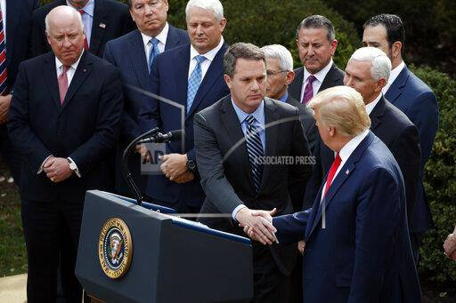 President Donald Trump shakes hands with Doug McMillon, president and CEO of Walmart Inc., during a news conference about the coronavirus in the Rose Garden at the White House on Friday in Washington.