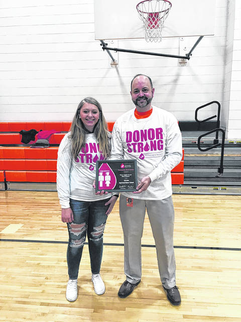 West Liberty-Salem Superintendent Kraig Hissong, pictured here with daughter Cathryn Hissong, holds the Community Blood Center's Red Cord Award, which was presented to the school for the number of its repeat donors. The superintendent and his daughter are two of these donors. The National Honor Society partnered with the CBC for the school's annual blood drive on Feb. 27. The CBC website states that students who register to donate blood at least three times while in high school earn a Red Cord to wear during graduation events.