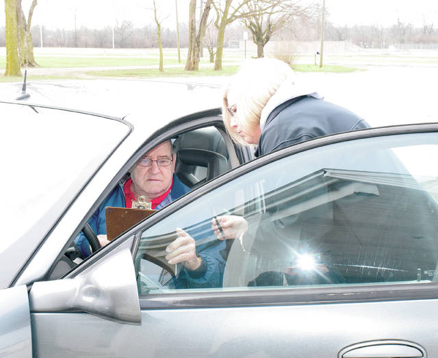 Tina Livingston takes an order from Robert Smith, who waits in his car while the volunteers inside the church gather his food and bring it out to him.