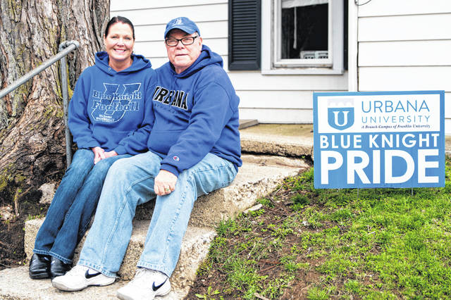 """The Beans of Urbana pose for a local photography project called """"Porchtraits"""" by John Coffman — who is depicting local families who are making the most of Ohio's stay-at-home orders to fight the spread of the COVID-19 pandemic. Pictured are Urbana Mayor Bill Bean and his wife Audra showing their Urbana University Blue Knight Pride. This is one of a series of """"Porchtraits"""" that will appear in the <em>Urbana Daily Citizen</em>. Other families who wish to be photographed are invited to contact Coffman directly on Facebook at his John Coffman Photography page, or text him at 937-206-0254."""