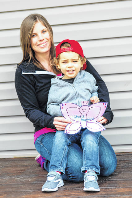 """The Eckstein family of Urbana poses for a local photography project called """"Porchtraits"""" by John Coffman — who is depicting local families who are making the most of Ohio's stay-at-home orders to fight the spread of the COVID-19 pandemic. Pictured in the theme """"Making memories with love"""" are Staci and Grayson Eckstein. Grayson and his mother made 3 different images: a butterfly, a flower, and hearts to hang up on the outside of every residence windows in an local area nursing home. This is one of a series of """"Porchtraits"""" that will appear in the <em>Urbana Daily Citizen</em>. Other families who wish to be photographed are invited to contact Coffman directly on Facebook at his John Coffman Photography page, or text him at 937-206-0254."""